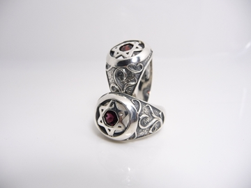 תמונה של טבעת כסף בשילוב מגן דוד כסף באמצע בשיבוץ אבן גרנט ועיטורים בצדדים